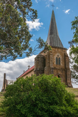 Richmond, Tasmania, Australia - December 13, 2009: Brown stone, red roof and gray spire of Saint Johns Catholic Church. Portrait from behind green bush upon entrance tower under blue sky.