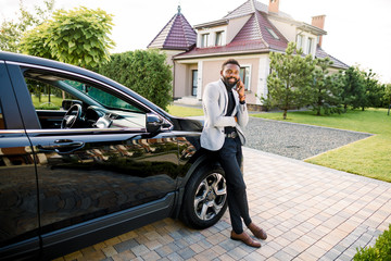 Handsome black businessman in a suit talking by smartphone near a black car, outdoors, building on the background