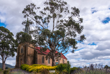 Richmond, Tasmania, Australia - December 13, 2009: Brown stone, red roof and gray spire of Saint Johns Catholic Church. Set in landscape with yellow flowers and green foliage under blue cloudscape.