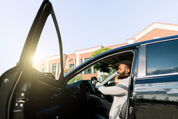 African American male boss businessman using smartphone for making call during while sitting in luxury car with open door, serious man concentrated phoning to partner. Side view