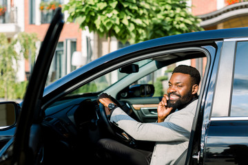 young African businessman sitting in his black car and making a phone call, and smiling. Office center buildings on the background