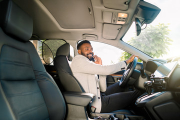 Black handsome business man driving the car talking on smartphone.