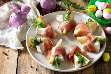 Festive snacks. Pear appetizer with jamon, arugula and brie cheese on a rustic wooden table.