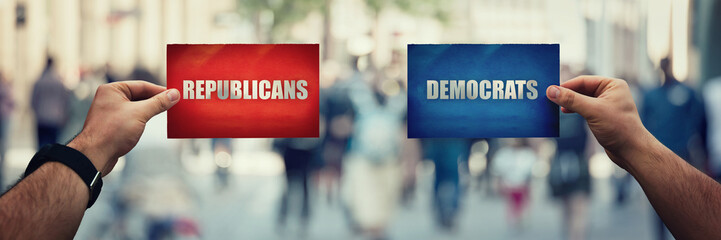 Two hands holding different colored paper sheet as Republicans versus Democrats political party over crowded street background. Future strategy concept red vs blue, Donkeys or Elephants symbols.