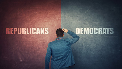 Puzzled businessman and a split wall with Democrats versus Republicans, red vs blue sides. Correct...
