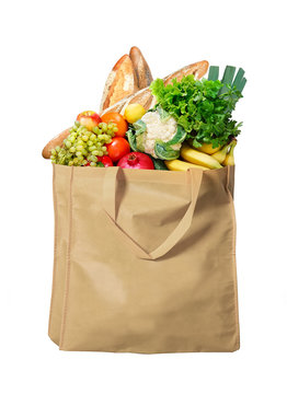 Eco friendly reusable shopping bag filled with bread, fruits and vegetables on a white background