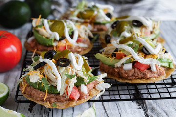 Chicken tostadas with refried pinto beans, fresh cilantro, shredded cheddar cheese, avocados, black olives, sour cream, lettuce, jalapenos, lime and tomatoes. Selective focus with blurred background.
