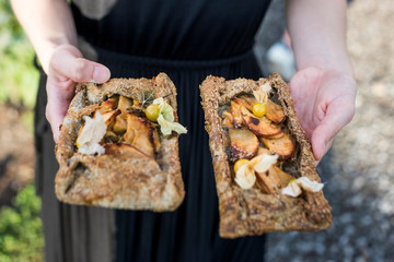 Women holding Buckwheat Pear Galettes with ground cherries and rosemary