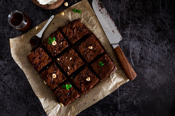 Homemade chocolate brownie dessert with hazelnuts, chocolate glaze and whipped cream on baking paper on a dark background. Top view. Horizontal orientation. Copy space.