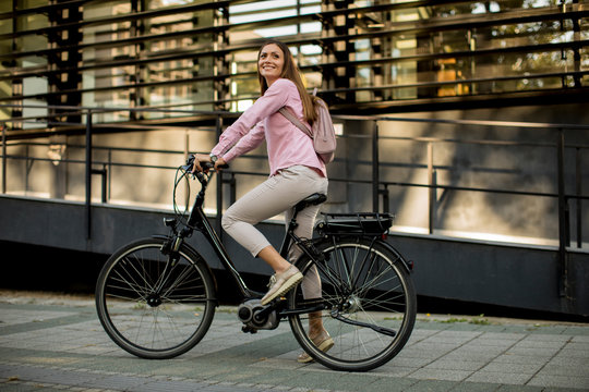 Young woman riding e bike in urban enviroment