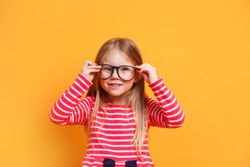 Portrait of young smiling girl wearing glasses on yellow background