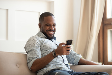 Cheerful african guy sitting on couch spending time using smartphone Fotobehang