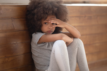 Sad african girl sitting on floor feels lonely closeup image