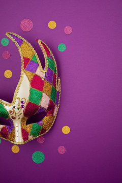 Festive, colorful mardi gras or carnivale mask and accessories over purple background. Party invitation, greeting card, venetian carnivale celebration concept. Flat lay, top view, copy space