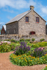 Stanley, Tasmania, Australia - December 15, 2009: Hightfield Historic Site. Flower garden adds color in front of gray stone house under blue cloudscape.