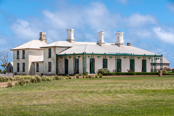 Stanley, Tasmania, Australia - December 15, 2009: Hightfield Historic Site. White with green trim main house with tall chimneys behind green lawn under blue cloudscape.