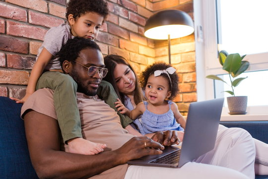 African dad and mom with two children sitting on the couch in the living room watching cartoons on a laptop. Son sitting on the neck of the Pope