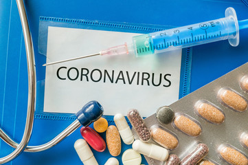 Novel coronavirus disease 2019-nCoV written on blue folder. Many pills, syringe and stethoscope.