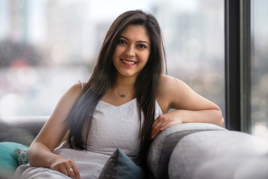 Beautiful headshot portrait of an indian, latina, hispanic woman, natural, friendly and charming bright smile with perfect teeth