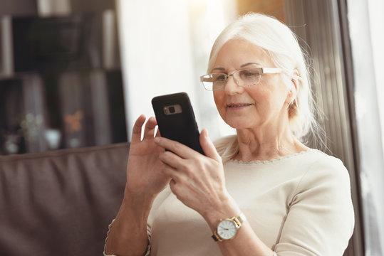 Beautiful senior woman texting at home