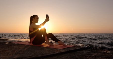 Young girl with long pony tail and a beautiful athletic body takes a selfie on the front camera on the background of the sea in the sunrise