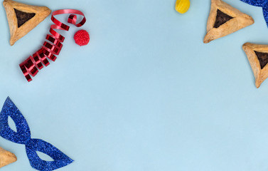 Triangular cookies with poppy seeds ( hamantasch or aman ears ), candy, glitter mask, serpentine for jewish holiday of purim celebration on blue background with space for text. Top view, flat lay