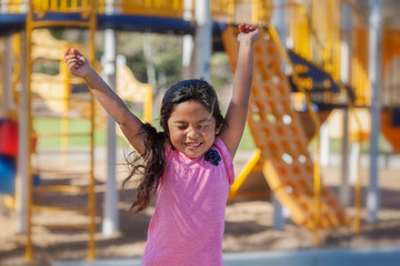 A cute latino girl jumping with joy as she plays in a kids playground. Fotomurales