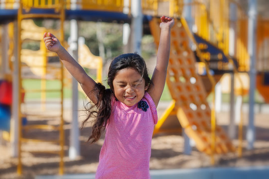 A cute latino girl jumping with joy as she plays in a kids playground.