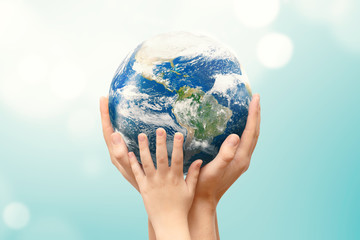 Earth globe in family hands. World environment day. Elements of this image furnished by NASA.