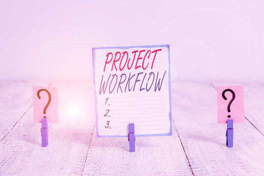 Writing note showing Project Workflow. Business concept for series of steps that need to be taken to complete tasks Crumbling sheet with paper clips placed on the wooden table