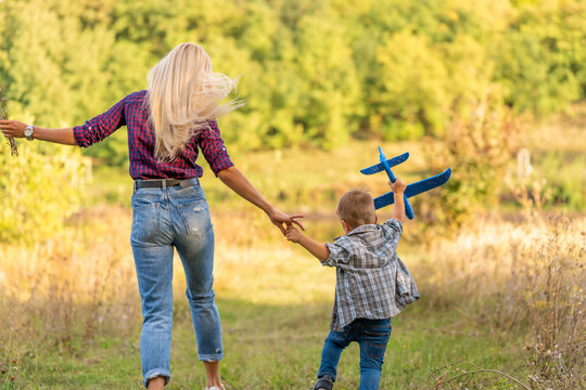 Little boy playing with toy airplane with his young mom outdoors at sunset. Happy Kid is playing in park outdoors.