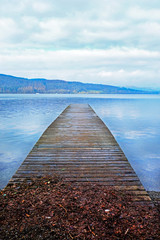 A long wooden jetty on a lake, looking out over a straight out over a clear calm blue lake