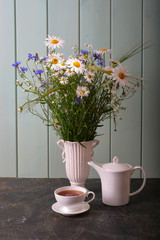 Tuinposter Lelie White cup with tea, white kettle and white vase with wildflowers cornflowers and daisies.