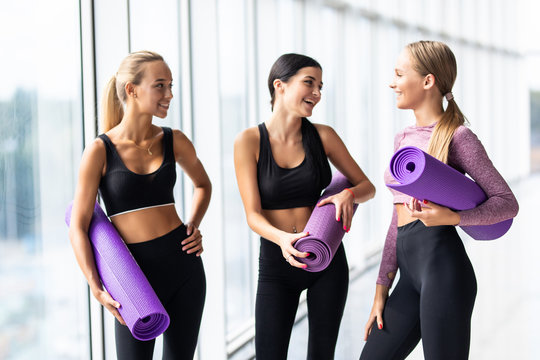 Three cheerful women talking with yoga mats standing in gym