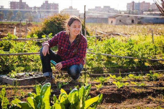 Young woman gardening in urban garden