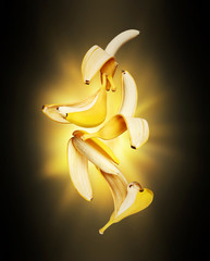 Open bananas in the air with flash of light in the dark
