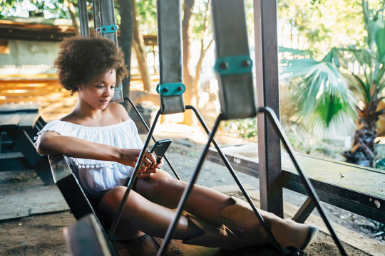 Woman sitting on porch swing in park text messaging on cell phone