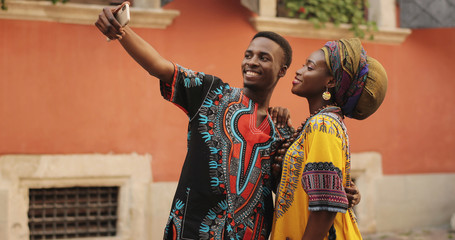 African young happy and good looking man and woman in traditional clothes standing together outdoor and taking selfie photos on the smartphone camera. Wall mural