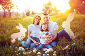 Little girl and her parents play with the rabbit. happy little girl holding cute fluffy Bunny. Friendship with Easter Bunny. Spring photo with beautiful young girl and her family with their Bunny.