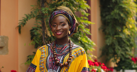 Portrait shot of the beautiful and happy Afrcan woman in the traditional outfit standing in the cozy courtyard with flowers and smiling to the camera. Outdoor. Fototapete