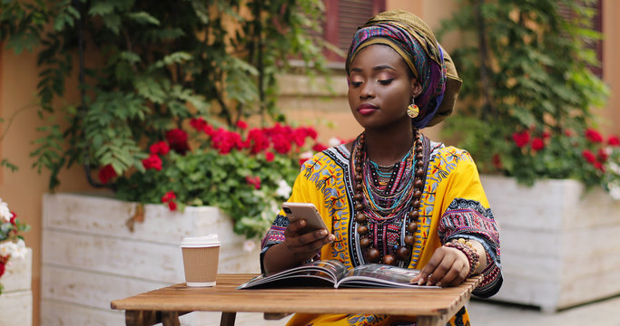 African pretty young woman in the traditional outfit talking on the phone cheerfully while sitting at the table wit magazine and coffee in the beautiful courtyard.