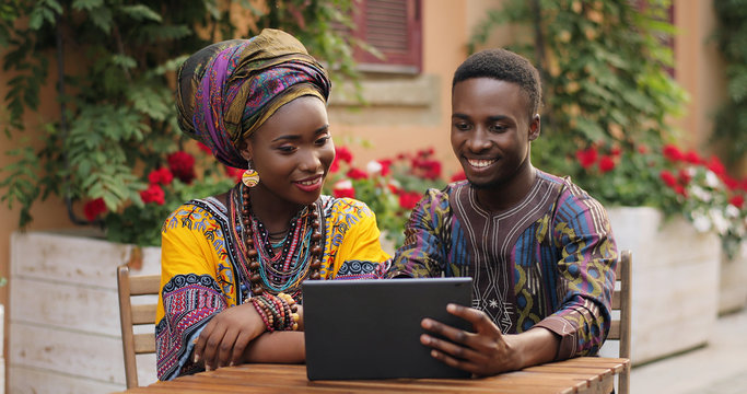 African cheerful young stylish man and woman in traditional outfits laughing while sitting at the table in the nice yard with flowers and watching something on the tablet computer.