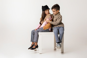 Cute stylish little couple girl and boy in fashionable clothes sittting together at studio. child boy hugs girl and tells her a funny story. kids fashion concept. Wall mural