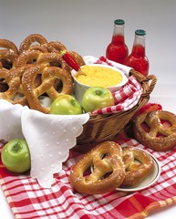 Vertical picture of pretzels on the table near lemonades and apples under the lights