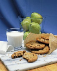Vertical picture of cookies on the table near a glass of milk and pears against a blue background