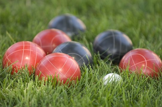 Picture of colourful bocce balls on the lawn under the sunlight with a blurry background