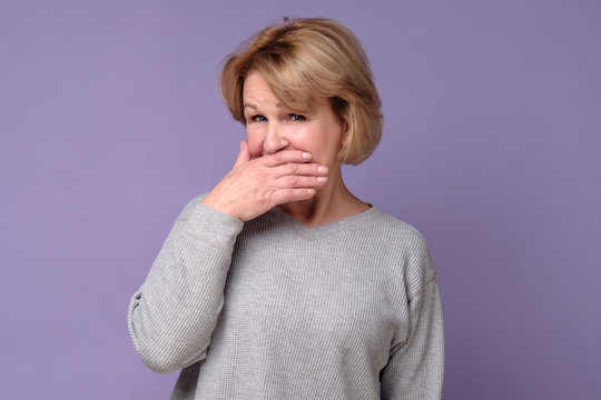 Senior older woman with puzzled look covering her mouth trying to keep secret. Studio shot