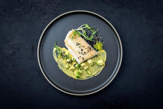 Gebratenes Kabeljau Fisch Filet mit Kaviar, Avocado Scheiben und Mango Senf Creme als Draufsicht auf einem Modern Design Teller mit Textfreiraum