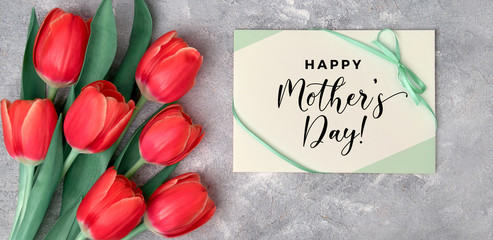 Happy Mother's day, flat lay with red tulips and paper card on grey textured background, modern panoramic top view, natural design with paper greeting card and fresh flowers.