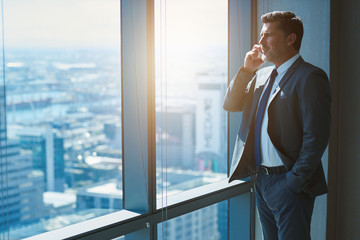Mature business CEO talking on phone alongside large high windows